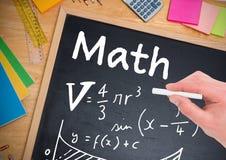 在有白垩的黑板在手中写的算术等式 库存图片