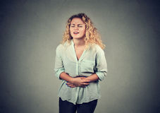 在有的胃的少妇手坏疼痛痛苦 免版税库存图片