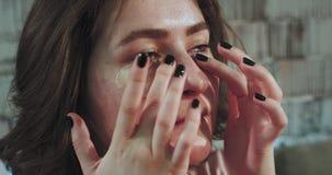 在有短发和斑点的照相机花姑娘前面在床前她做她自己的眼罩,看 股票录像