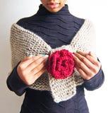 在有红色玫瑰的浅褐色的羊毛围巾包裹的女孩 免版税库存照片