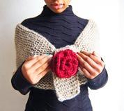 在有红色玫瑰的浅褐色的羊毛围巾包裹的女孩 库存图片