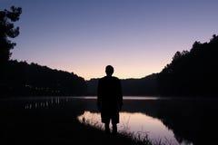 在有美丽的暮色天空的湖供以人员立场 免版税库存图片