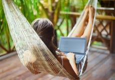 在有膝上型计算机的一个吊床的少妇在一种热带手段 免版税库存照片