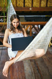 在有膝上型计算机的一个吊床的少妇 免版税图库摄影