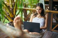 在有膝上型计算机的一个吊床的美丽的妇女在热带res 图库摄影