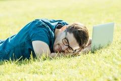 在有膝上型计算机的公园的疲乏的自由职业者 免版税库存照片