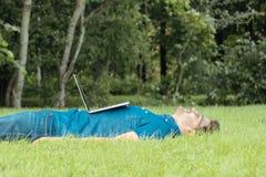 在有膝上型计算机的公园的疲乏的自由职业者 库存图片