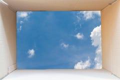 在有蓝天的棕色纸板箱里面 免版税库存图片