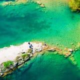 在有蓝色天蓝色的水ang人的岩石岬的对此的一顿野餐 免版税库存照片