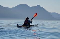 在有蓝色山、海洋和天空的西北温哥华岛附近供以人员桨海皮船在冒险的镇静夏天早晨 免版税图库摄影