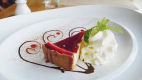 在有薄菏奶油和叶子的一块白色板材乳酪蛋糕美丽服务的可口切片  图库摄影