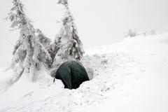 在有薄雾的冬天横向的雪埋没的帐篷 库存照片