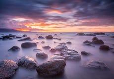 在有薄雾的岩石的日落 免版税库存照片