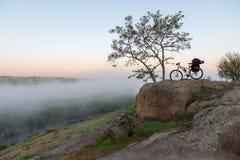 在有薄雾的峡谷、河和石头的自行车 图库摄影