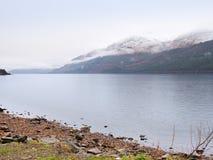 在有薄雾的日落前的Mountain湖在Higland在苏格兰 山斯诺伊锥体在反映水上的 库存图片