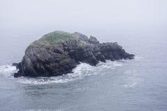 在有薄雾的海的岩石小岛 库存照片