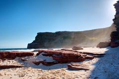 在有薄雾的海滩的红色岩石 免版税库存照片
