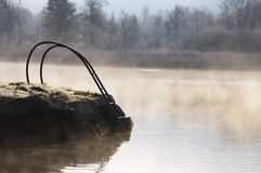 在有薄雾的Winter湖的铁梯子 免版税库存照片