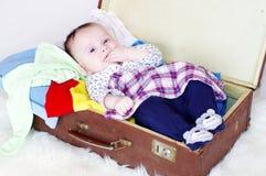 在有衣裳的一个老手提箱的愉快的婴孩 免版税库存照片