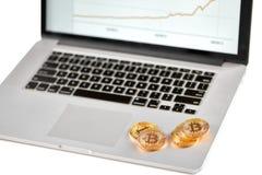 在有被弄脏的财政图的银色膝上型计算机安置的堆金黄bitcoins在它的屏幕上 免版税图库摄影