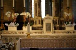 在有被点燃的法坛和蜡烛的一个教会里面 免版税图库摄影