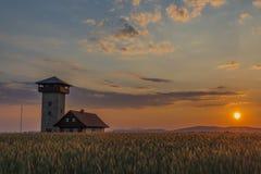 在有观测塔的Roprachtice村庄附近上色日落 免版税库存图片