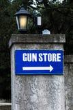 在有轻的岗位的一个石墙上张贴的木枪店标志 免版税库存照片