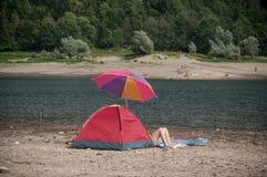 在有野营的帐篷的边界湖结合坐 库存图片