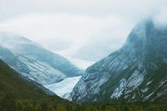 在有雾挪威的山的Nigardsbreen冰川 免版税库存图片