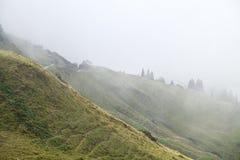 在有雾的山的小木客舱 免版税库存图片