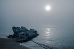 在有雾的日落的岩石 库存照片