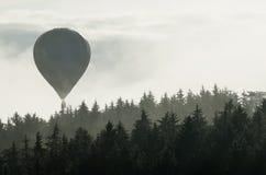 在有雾的森林上的热空气气球 免版税库存图片