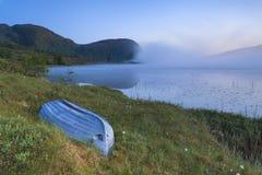 在有雾的湖的看法有在岸的小船的 免版税库存照片