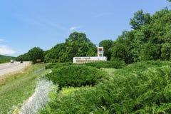 在有题字的绿色植物围拢的路旁的石碑用俄语:英雄市新罗西斯克 库存图片