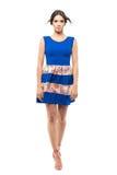 在有风蓝色夏天短小礼服的俏丽的时装模特儿有看照相机的飞行头发的 免版税库存图片
