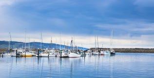 在有风雨如磐的天空的小游艇船坞停住的游艇 免版税库存图片
