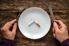在有香烟的一块白色板材旁边供以人员拿着刀子和叉子 库存图片