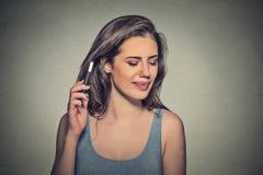 在有头疼的电话生气的妇女 生气不快乐的女孩谈话在电话 免版税图库摄影