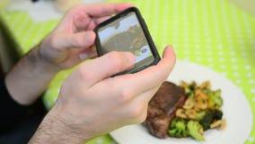在有他的电话的餐馆供以人员拍摄食物 股票视频