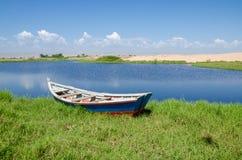 在有绿草和沙丘的盐水湖停住的渔船 免版税库存照片