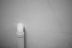 在有破裂的白色墙壁上附有的一个白色管子 库存照片
