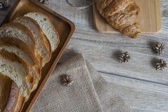 在服务的一张木桌和新月形面包安置的长方形宝石 免版税库存图片