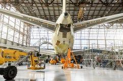 在服务的客机在尾巴的航空飞机棚背面图,在辅助电源设备 免版税库存图片