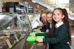 在服务的线附近的孩子与在学校cantee的健康食品 图库摄影