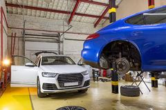 在服务站的两辆汽车在轮子的季节性变动 库存图片