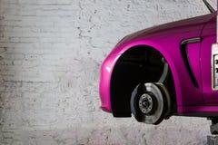 在服务站的桃红色sportcar汽车轮胎的停止 库存照片