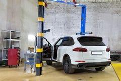 在服务站的白色德国SUV 在维护下 免版税库存照片
