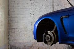 在服务站的蓝色汽车轮胎和轮子替换的 库存图片