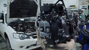 在服务自动聚焦里面引擎在一辆白色汽车前面垂悬 股票录像