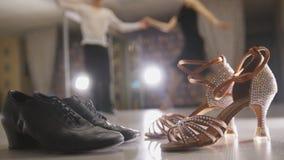在服装在演播室,在前景的两双对舞厅鞋子的被弄脏的专业男人和妇女跳舞的拉丁舞蹈 库存图片